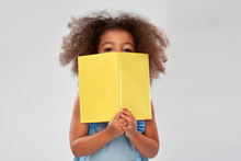 Childhood, School And Education Concept - Happy Little African American Girl With Book Over Grey Background