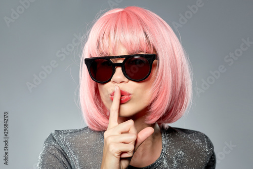 Photo fashion, silence and secret concept - young woman in pink wig and black sunglass