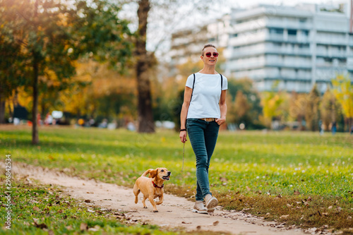Fototapeta Woman walking in the park with a dog in autumn obraz