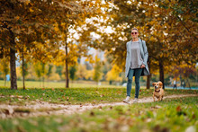 Happy Woman Walking On A Park Trail With A Small Brown Dog In Autumn