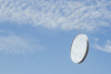 Round Mirror In Blue Sky Reflecting Clouds