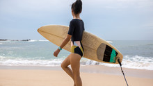 Woman Surfer Walking With Surfboard On The Beach