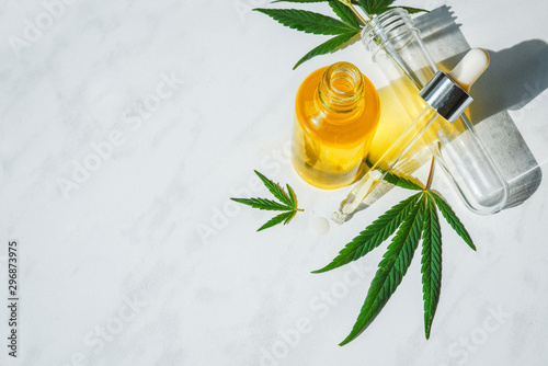 Glass bottle with cannabis oil and a test tube with hemp leaves on a marble background Canvas Print