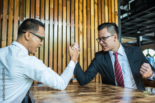 Vászonkép Two Asian businessman expressed a serious expression and fighting by used arm wrestling on wood table
