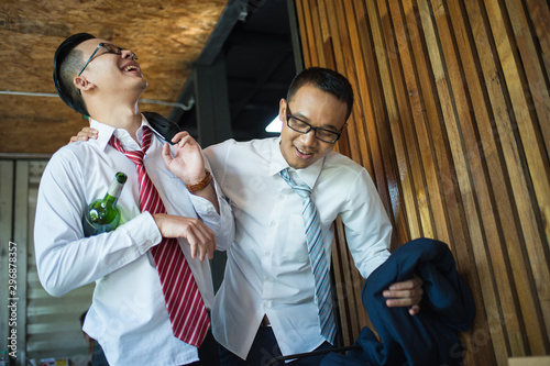 Fototapeta two businessman is drunk and laughing after drinking hard in restaurant to celebrate the success of work