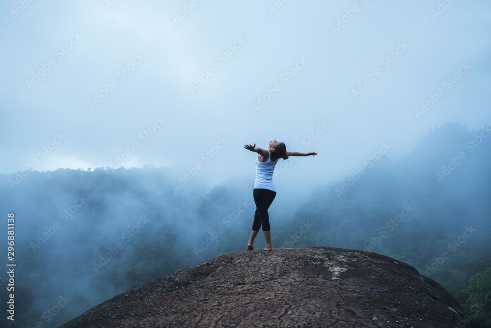 Fototapety, obrazy: Young woman exercises yoga in the mountains. Asian woman travel nature. Travel relax exercises yoga touch natural fog on mountain peak.