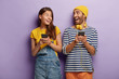 canvas print picture - Joyful boyfriend and girlfriend laugh and look at each other, hold mobile phones, send text messages, surf internet webpage, read news about sales, play video games, have fun and watch video