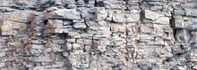 Rock Cliff Face Background. Dangerous Vertical Wall With Protruding Crumbling Layered Stone Blocks In Quarry For The Extraction Of Wild Stone. Abstract Texture For Stone Mining Industry