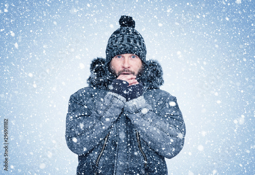 Valokuva  Frozen bearded man in winter clothes warms his hands, cold, snow, frost, blizzar