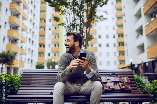 laughing handsome stylish businessman typing message on smart phone while sitting on the bench in park Canvas Print