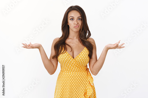 Fotografie, Tablou Picky displeased arrogant young brunette in yellow dress, shrugging raise hands