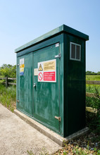 Rural Electric Pumping Station And Control Cabinet Seen At The Edge Of An English Village. Showing Warning Signs On The Green Metal Closet.