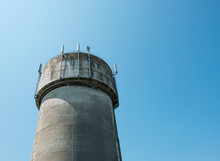 Large Concrete Water Tower Showing Mobile Phone Communications Antennas Attached.