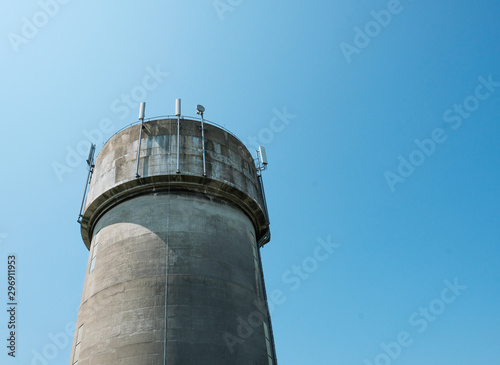 Photo Large concrete water tower showing mobile phone communications antennas attached