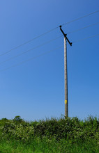 Wooden Telegraph Pole Seen In Isolation Against A Clear Blue Sky At The Edge Of A Village.