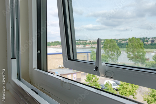 Close-up view of an opened, double glazed window seen in a private apartment, looking out to further buildings and a river in the distance Wallpaper Mural