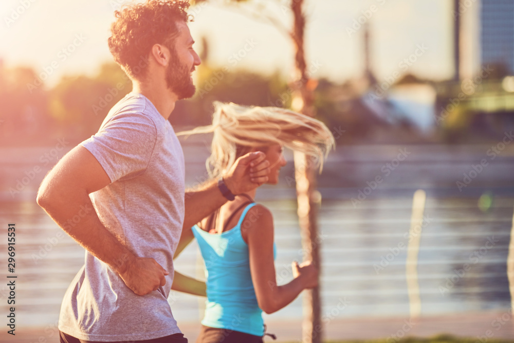Fototapety, obrazy: Modern woman and man jogging / exercising in urban surroundings near the river.