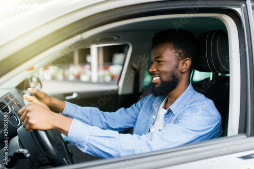 Happy young african american man driving a car on street roads Canvas Print