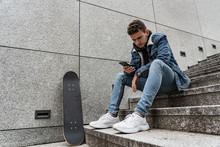 Young Man Sitting With Saketeboard On Stairs
