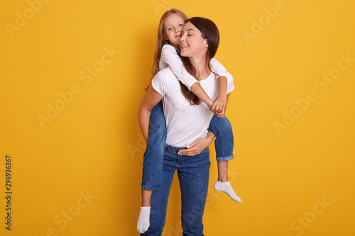 Fotomural  Studio shot of beautiful young brunette mother holds on back her cute little blonde daughter in white shirt and overalls, female dresses t shirt and jeans, posing isolated over yellow background