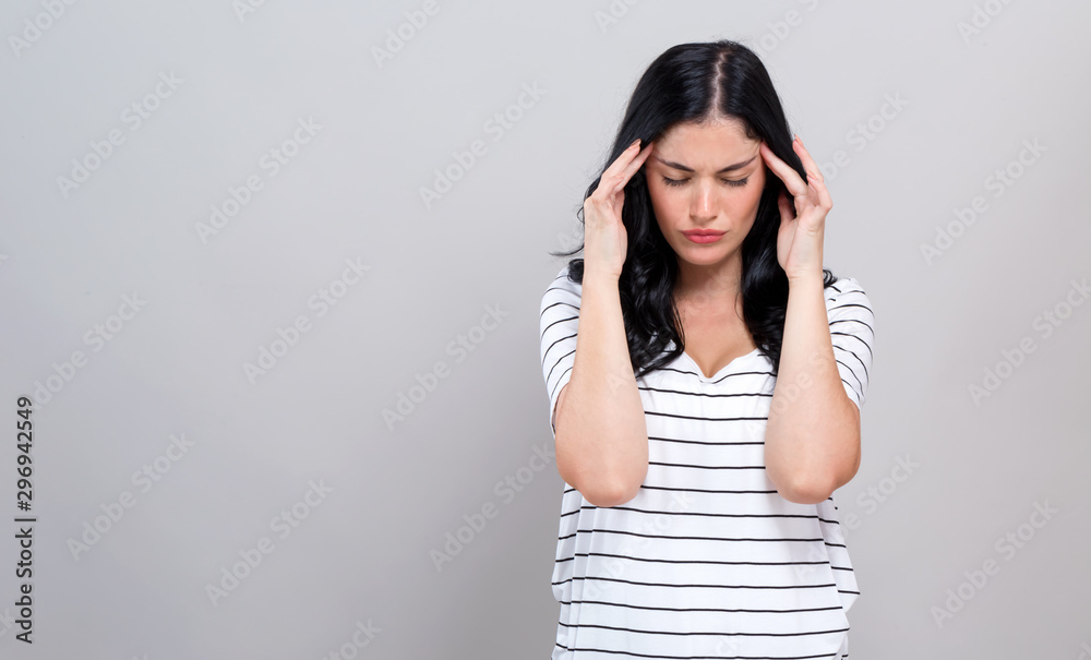Fototapety, obrazy: Young woman suffering from headache on a gray background