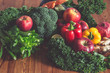 Fresh organic raw groceries: vegetables, fruits and greens on a wooden table
