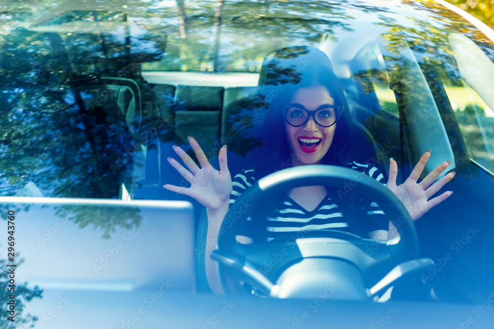Fototapety, obrazy: Woman in a self-driving autonomous electric vehicle with hands off the steering wheel