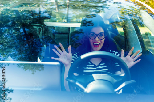 fototapeta na ścianę Woman in a self-driving autonomous electric vehicle with hands off the steering wheel