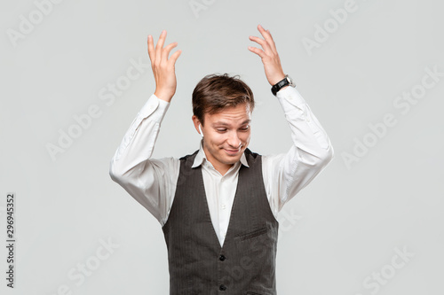 Young businessman in a white shirt and grey vest shrugging his shoulders expressing emotion of confusion Canvas Print