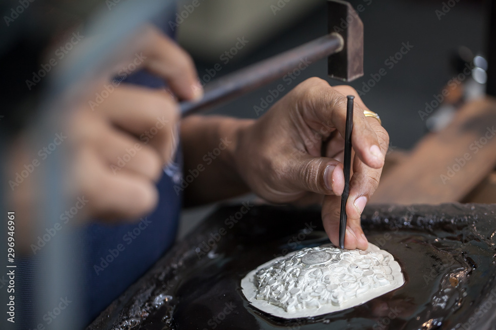 Fototapety, obrazy: Silversmith using hammers and steel engraved  pattern on silver plate for accessory handmade