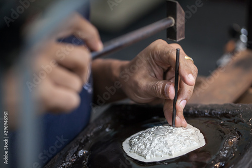 Photo Silversmith using hammers and steel engraved  pattern on silver plate for access
