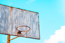 Vintage Old Basketball Hoop With A Wooden Board With Peeling Paint On The Background Of Blue Sky
