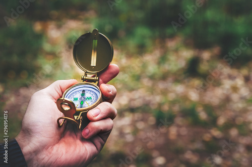 Fotografie, Obraz A man holds a compass and a paper map in his hand and is guided by the area, aut