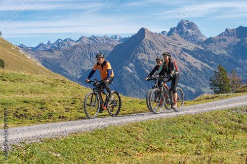 Deurstickers Fietsen three happy senior adults, riding their mountain bikes in the autumnal atmosphere of the Bregenz Wald mountains near Mellau, Vorarlberg, Austria