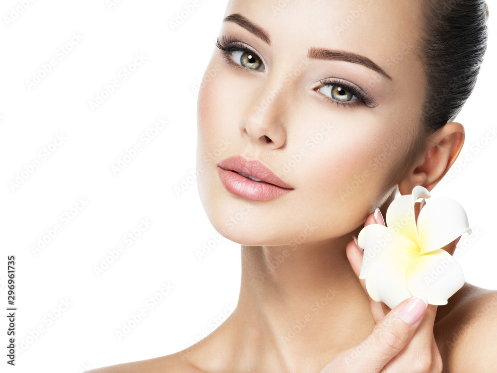 Fototapeta Beautiful face of young woman with flower