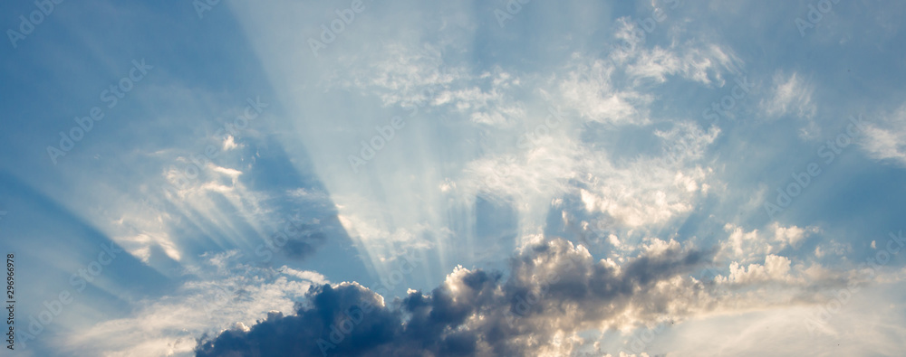 Fototapeta the sun's rays breaking through the clouds in straight lines, against a background of blue sky and thunderclouds