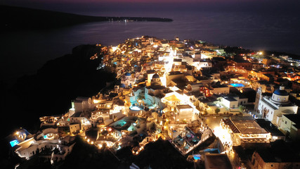 Aerial drone night shot of beautiful illuminated traditional and picturesque village of Oia built on a cliff, Santorini island, Cyclades, Greece