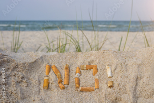 Obraz na plátně  in the foreground, the word no! written in the  sand with cigarette stubs,  th