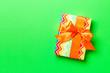 Leinwandbild Motiv Top view Christmas present box with orange bow on green background with copy space