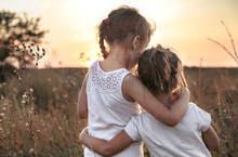 Two Little Sisters In A Field At Sunset.