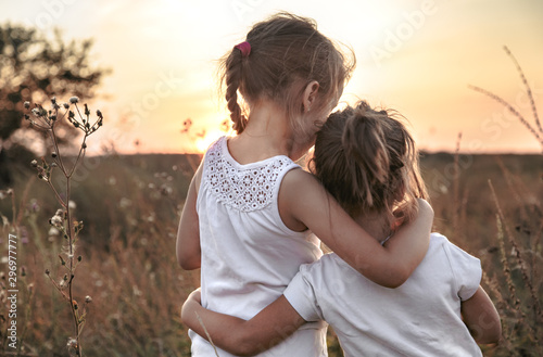 Two little sisters in a field at sunset. Tablou Canvas