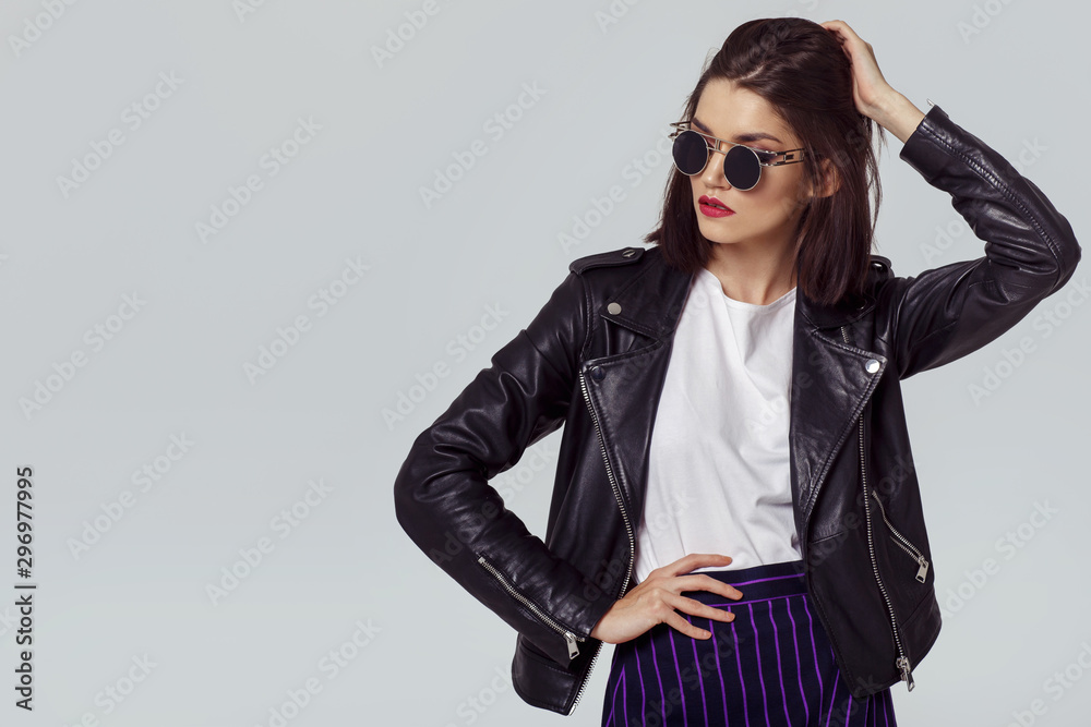 Fototapeta Fashion portrait of a young woman in leather jacket.