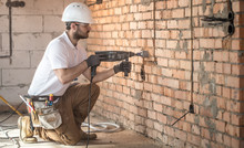 Handyman Uses Jackhammer, For Installation, Professional Worker On The Construction Site. The Concept Of Electrician And Handyman.