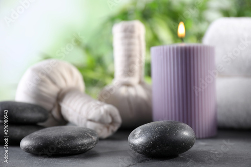 Foto op Plexiglas Spa Composition with stones and spa accessories on black table against blurred background. Space for text