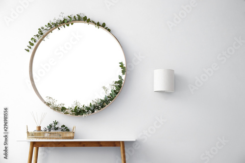 Poster Fleuriste Round mirror and table with accessories near white wall in modern room interior