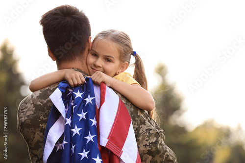 Foto Father in military uniform with American flag and his daughter at sunny park