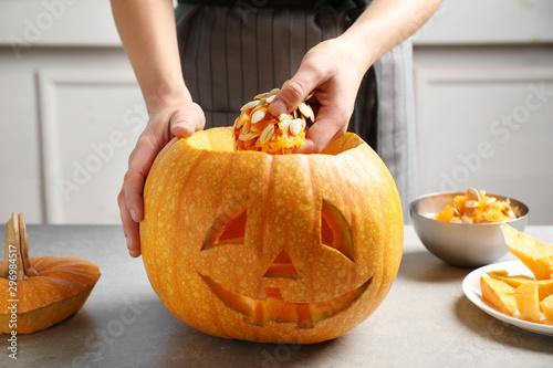 Fotomural  Woman making pumpkin head Jack lantern for Halloween at light table indoors, clo