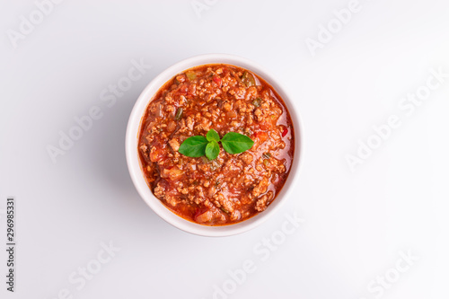 Photo Bolognese (also know as Bolognesa or Bolonhesa) sauce in a white bowl isolated i