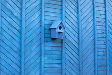 Blue Birdhouse On A Blue Wooden Wall