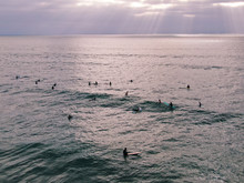 Aerial View Of Surfers Waiting, Paddling And Enjoying Waves Before Sunset Time. Del Mar Beach, California, USA